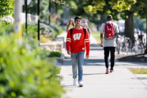 A pedestrian wearing a Motion W-branded shirt walks along Linden Drive near Agricultural Hall.