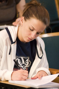 Image of an undergraduate student in a lecture hall wearing a t-shirt with Bucky on it.