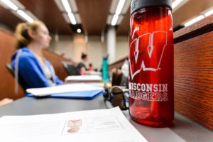 A student's Wisconsin-branded water bottle and pair of sunglasses are pictured as the student takes notes during a Kinesiology class in the Education Building.