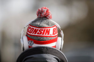 A student wearing headphones and a Wisconsin hat with a logo of mascot Bucky Badger walks down Bascom Hill.